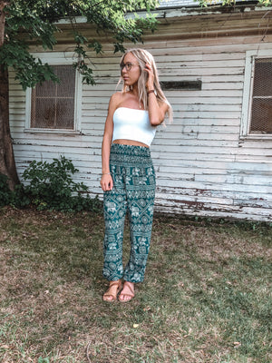 A girl poses in a cute white top and teal elephant harem pants.