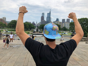 A traveler conquers the Rocky steps in Philadelphia in his Active Roots hat.
