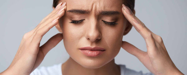 Woman holding head with migraine