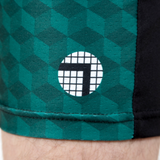 "Close up of ATK Apparel logo on pine green Performance Shorts (cube pattern). Perform better with a better fit: rise and inseam tailored for men 5'8"" and under."