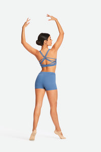 Full body picture of a dancer on demi pointe wearing a matching blue Capezio crop top and shorts
