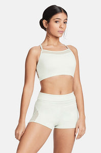 Dancer with hair in a bun posing in a lace insert Capezio crop top and shorts