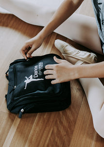 Ballerina sitting on a wooden dance floor with a bent leg, hands are unzipping black makeup bag that has Dance Dynamics white logo on the front