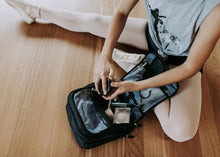 Ballerina sitting on a wooden dance floor with a bent leg, hands are taking makeup out of a black makeup bag that has Dance Dynamics white logo on the front