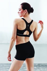 Dancer slightly looking back over her shoulder, hair in a bun, right arm bent up wearing Capezio crop top and shorts