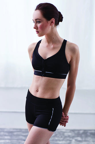 Sporty looking dancer wearing black Capezio crop top and shorts with white piping trim, hands clasped behind her back
