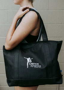 Black Dance Dynamics tote bag hanging over the shoulder of a girl. Her arm is bent and her face is not shown