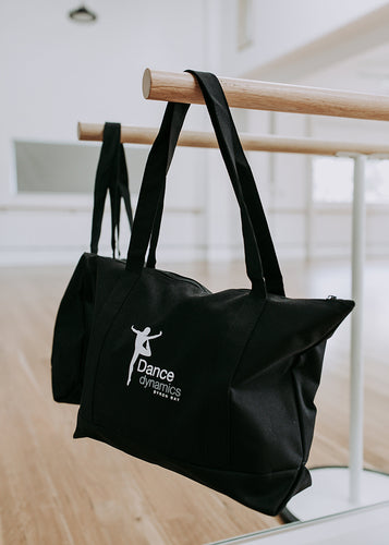 Black Dance Dynamics dancewear tote bag hanging on the end of a barre