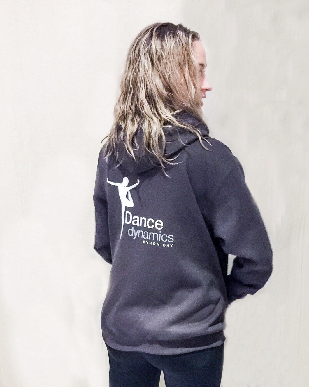 Woman with blonde messy hair standing back on showing Dance Dynamics logo on the back of a charcoal hooded sweater