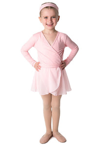 Smiling child ballerina with hands on hips wearing a pink Studio 7 crossover top, pink headband and pink chiffon wrap skirt