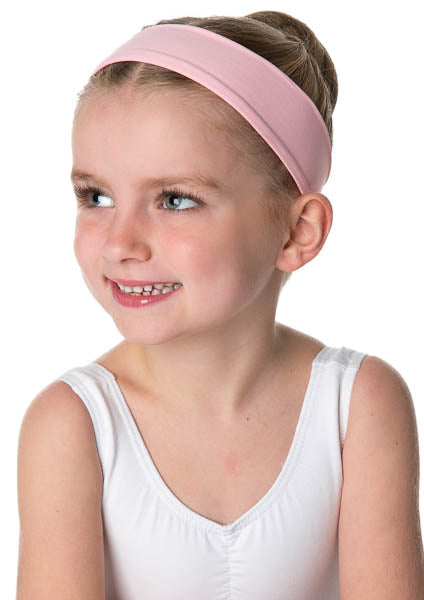 Smiling young ballerina wearing a white leotard and pink headband