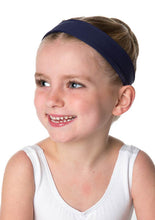 Smiling child ballerina wearing white leotard and black head band