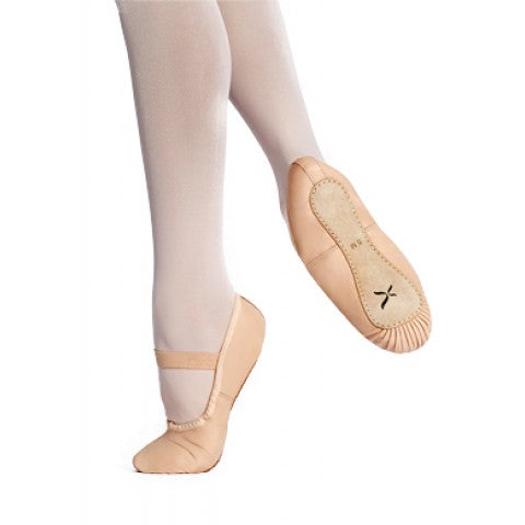 Feet wearing Capezio Clara ballet slippers with one foot on demi pointe with other foot behind with sole of the shoe showing