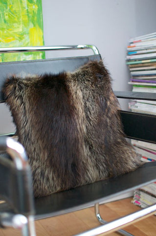 A fur throw pillow sits on a chair with a stack of books in the background.