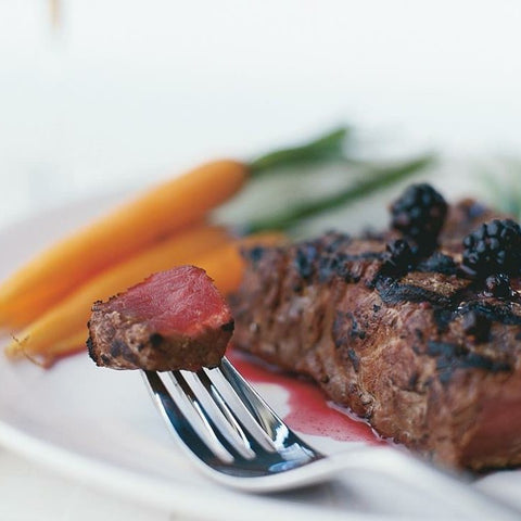 A cut of bison steak, cooked medium rare, with steamed carrots on the side.