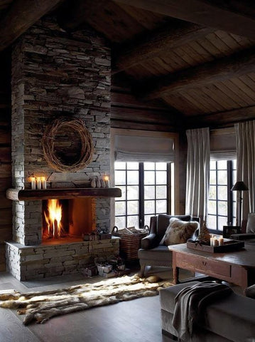 A simple, rustic room is empty, with a large fireplace made of stone bricks taking up most of the space.