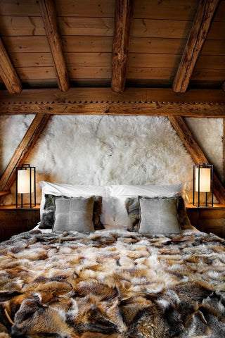 A bed covered in a fur comforter with fur lined walls.