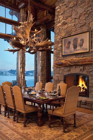 A lovely dining area with a stone mantle, antler chandelier, and a view of mountains in the background.