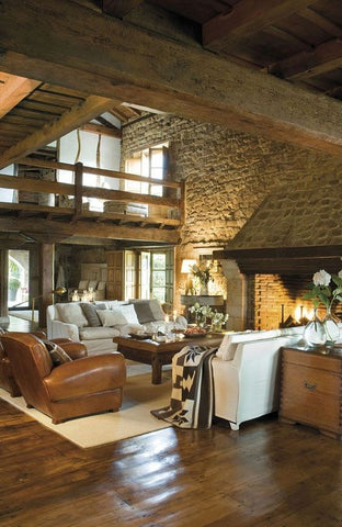A large, rustic livingroom with stone walls and some modern furniture filling space in front of the mantle.