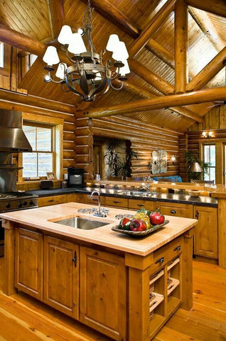 A large cabin kitchen with a bright wood island in the center and plenty of light. An a-frame dissects the room.