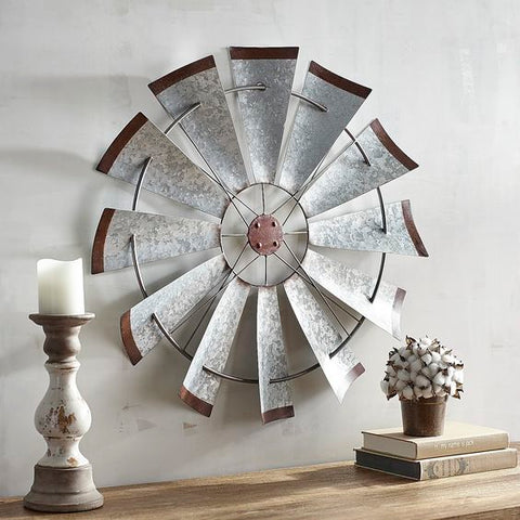 An old windmill fan hangs on a simple white wall.