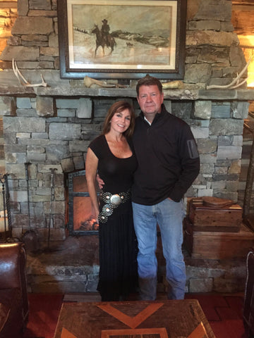 Dr. Chriss Mack stands next to his wife in front of a stone fireplace in their home.