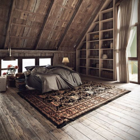 A large, open bedroom with a large area rug and windows letting in a lot of natural light.