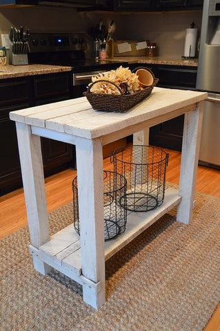 A kitchen island made out of repurposed wood, painted white, with a basket of flowers sitting on it.