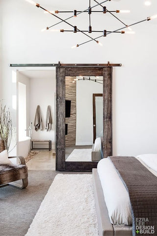 A bedroom with mostly white walls and furniture, well lit and accented by reclaimed, dark wood being used as the borders to a mirror.