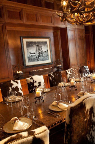 A dining table lined with chairs covered in cow hide, empty plates sit in front of candles, under a chandelier of antlers. On the wooden wall, a bovine portrait is hanging.