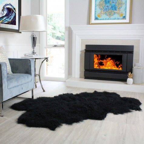A sheepskin rug lays in front of a simple metal fireplace.