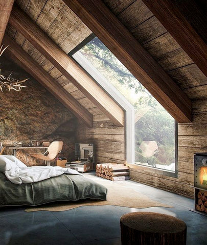 A bedroom in a cabin with a large, angled window letting in lots of light on a simple bed, desk, and area rug.
