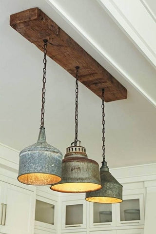 Rusting cans cut in half are used as light bulb shades hanging from the ceiling.