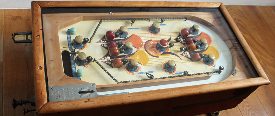 close up of pinball machine coffee table showing original brass levers and knobs and lovely original colours orange, yellow blue