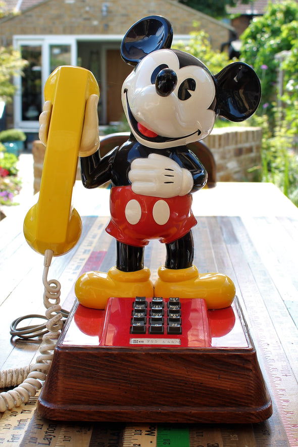 Vintage Mickey Mouse telephone, holding large yellow receiver, looking very happy in sunny garden