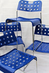 4 blue Omstak chairs stacked on top of each other, showing shiney blue metal seats and back and chrome frames