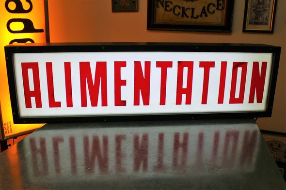 Large lit lightbox with ALIMENTATION in tall red capital letters again white background and black framed boxing.