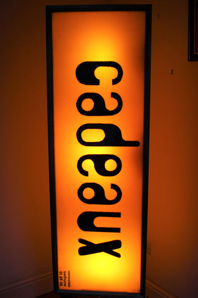 Large lit vintage shop sign spelling CADEAUX vertically downwards, black retro lettering on orange backround, gives warm glow to the room
