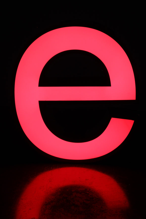 Lit letter e giving lovely pink colour and warm red reflection on table