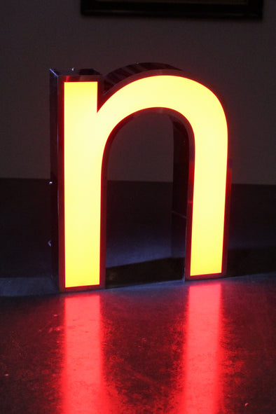 Lit letter n glowing and giving lovely red reflection on table