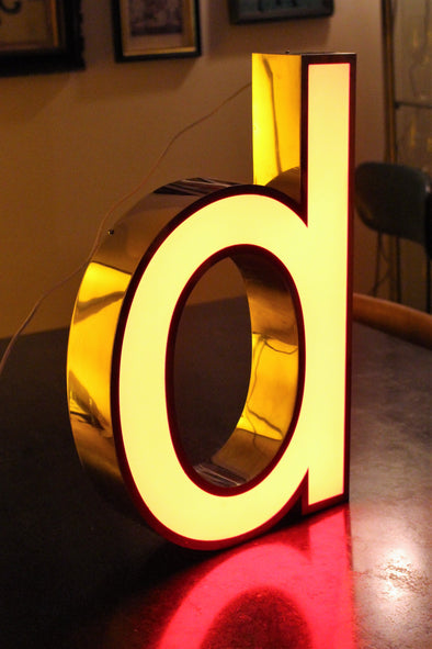 Lit letter d showing red reflection, shiney chrome sides and giving a warm glow to the room