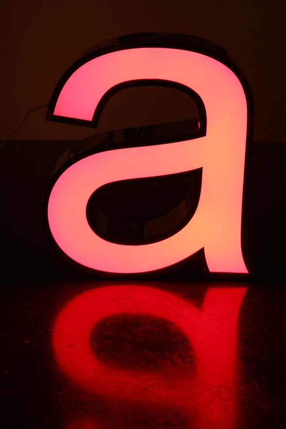 Lit letter a showing red reflection and pink warm glow