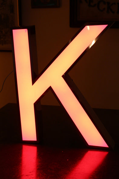 Lit letter k showing warm pink colour and red reflection on table