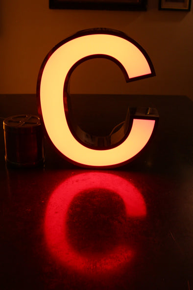 Lit letter c showing red reflection and warm glow in room