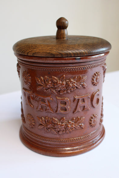 Round brown glazed jar with TABAC lettering and flower detailing around, turned wood lid.