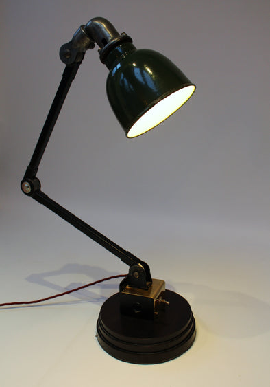 Angle poise task lamp, lit, showing dark green lamp shade and solid wood base