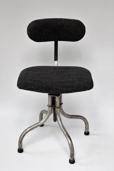 Tansad factory chair front on, showing seat and back reupholstered in dark grey wool, turned out metal legs