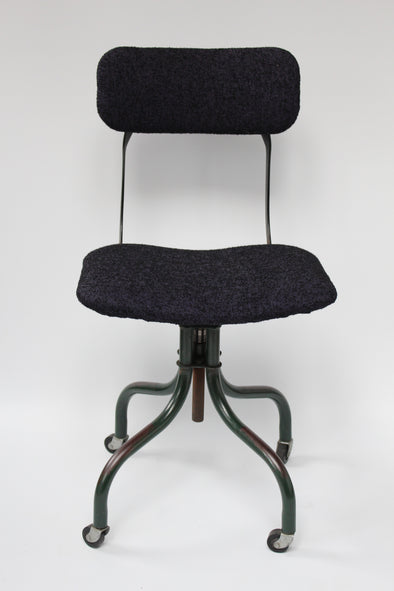 Tansad factory chair front on, showing seat and back reupholstered in blue boucle material, chair sits on 4 outward turns legs with castors
