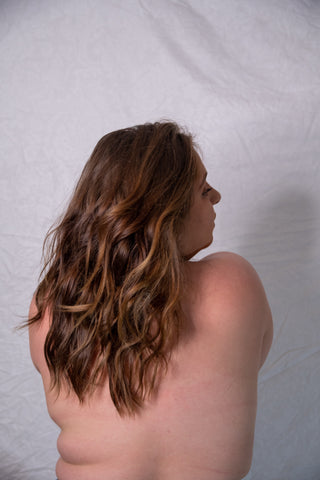 Naked women's back with arms wrapped around her front