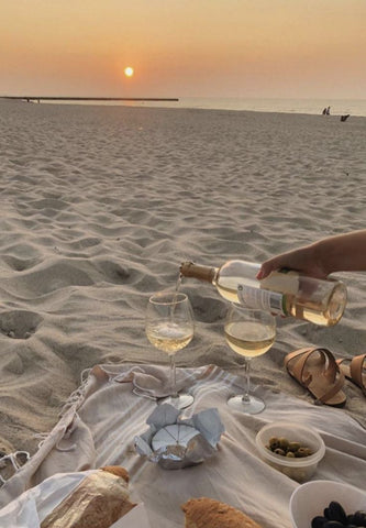 Wine and picnic on the beach with a sunset